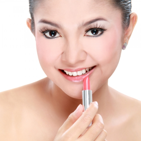 attractive woman portrait on white background applying lipstick photo