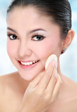 beautiful young asian woman with cotton pad applying face powder photo