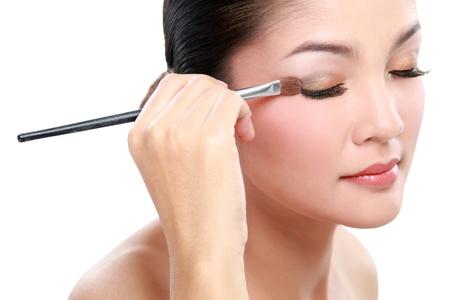 eyelid: Beautiful young woman applying eyelid make up with make up brush Isolated on white background