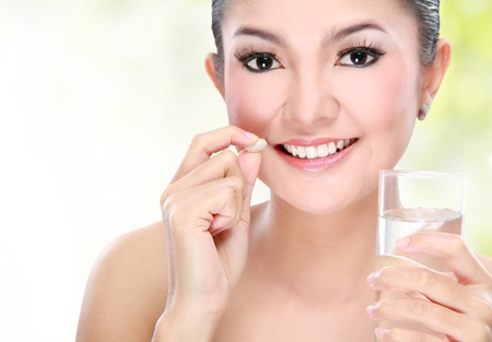 Portrait of a beautiful asian young woman taking vitamin tablet photo