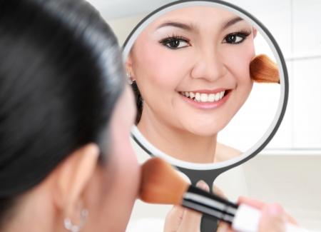 mujer maquillandose: Reflexión de la cara de la mujer hermosa en el espejo usando maquillaje cepillo en su habitación Foto de archivo