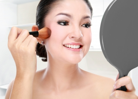 Reflection of beautiful woman face in mirror using make up brush in her room