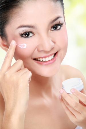 Close up portrait of beautiful women applying moisturizer cosmetic cream on face photo