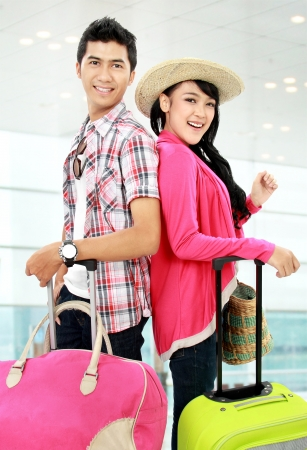 Happy teenagers tourist going on vacation with suitcase and smile photo
