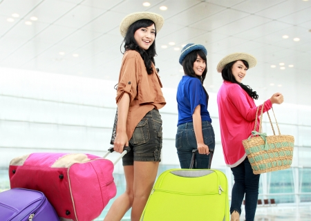 arrive: portrait of Happy girls going on vacation walking with suitcase and smile