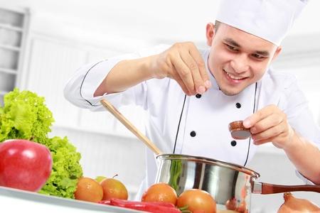 gelukkig lachende mannelijke chef-kok koken in de keuken