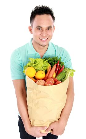 Portrait of smiling young asian Man with paper bag full of fruits and vegetables isolated on white background photo