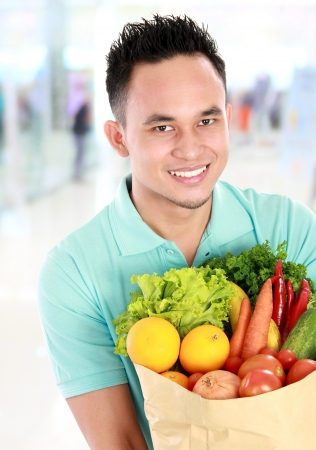 health food store: Portrait of smiling young asian man holding grocery bag full of groceries in supermarket
