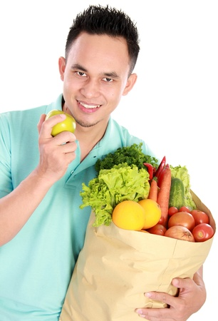 smiling young man holding shopping bag full of groceries isolated against white background photo