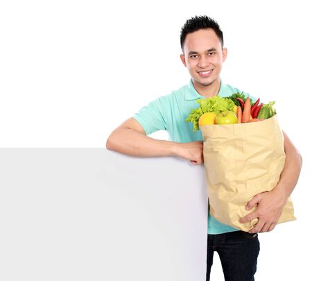 Portrait of smiling young man with paper bag full of fruits and vegetables holding blank big board photo