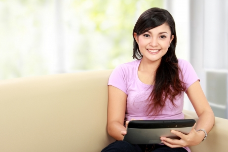 lifestyle home: happy asian woman using tablet pc while sitting on the couch