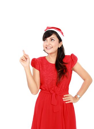 Woman with santa hat in red dress pointing up - isolated on white background. photo
