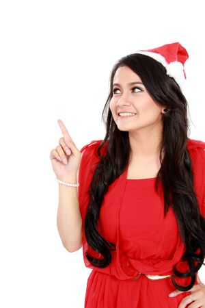 Woman with santa hat in red dress pointing up - isolated on white background. Stock Photo - 16800581