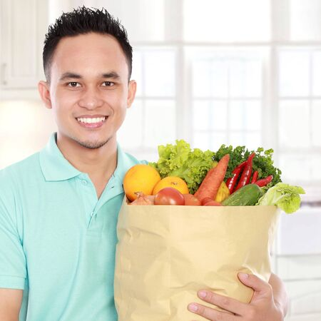 smiling young man holding shopping bag full of groceries in the kitchen ready to cook Stock Photo - 16800586