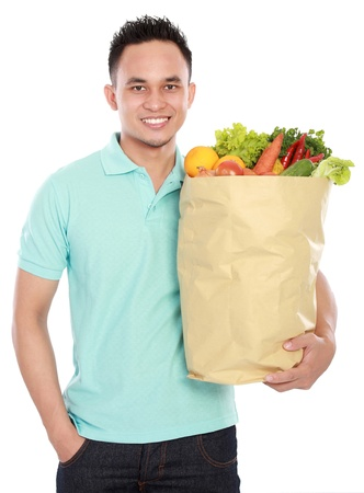 smiling young man holding shopping bag full of groceries isolated against white background Stock Photo - 16800593