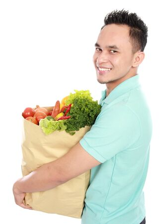 Portrait of smiling young asian Man with paper bag full of fruits and vegetables isolated on white background Stock Photo - 16800587