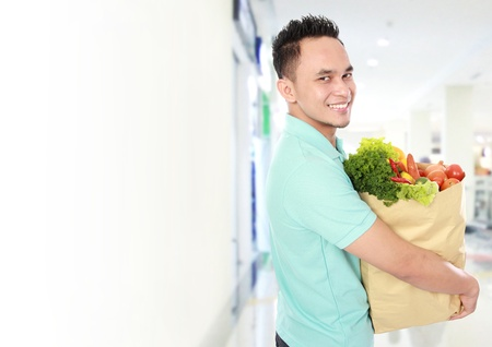 Portrait of smiling young man holding grocery bag full of groceries in supermarket Stock Photo - 16800607