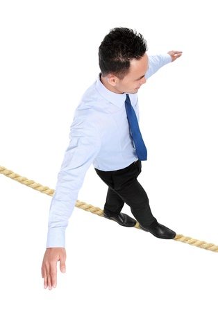 businessman crossing the small rope isolated on white background photo