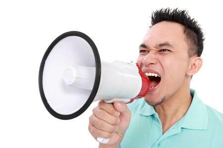 loud: close up portrait of young man shouting using megaphone isolated on white background