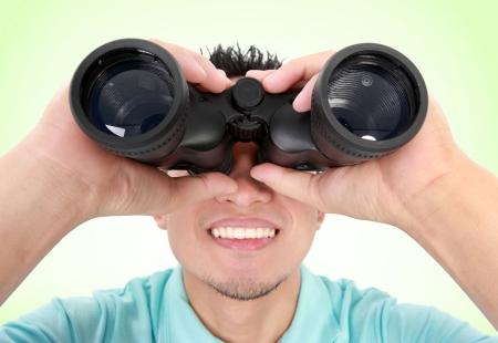 Portrait Of A Young Man With Binocular Over A Green Background photo