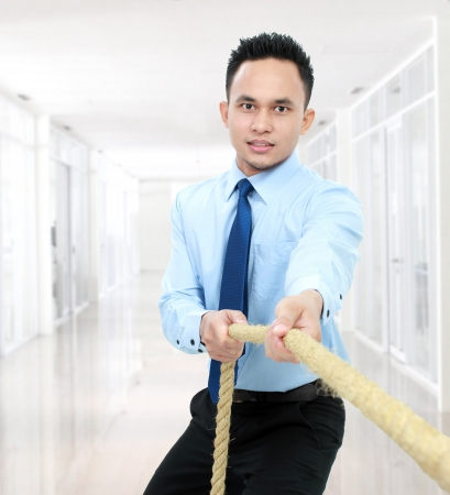 male executive man pulling a rope in the office Stock Photo - 16800538