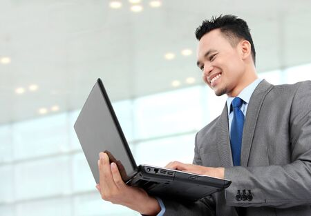 young business man using laptop while standing at the office photo
