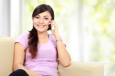 Young happy asian woman is calling with a mobile phone while sitting on the couch Stock Photo - 16800580