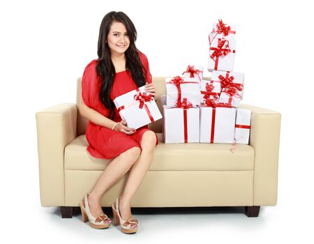 smiling woman with many gift box sitting on couch Stock Photo - 16800512
