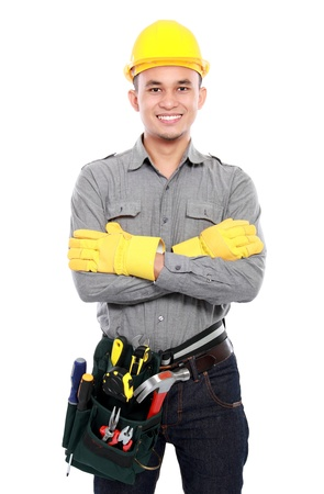 protective workwear: smiling worker crossed his arms and bring equipment ready to work Stock Photo