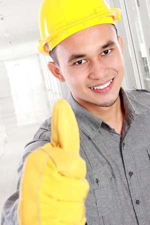 Portrait of young worker  giving you thumbs up photo