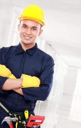 worker use blue uniform crossed his arms and belt tools and crossed his arms photo
