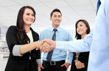 estrechando manos: Estrechar la mano de dos hombres de negocios en la oficina