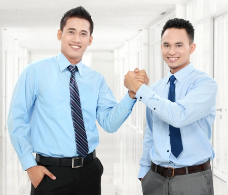 Portrait of two happy business men shaking hands with each other in office photo