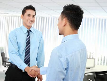 pacto: Retrato de hombre de negocios exitoso estrechar la mano entre nosostros en la oficina