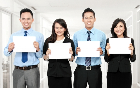 business team holding small blank paper in the office photo