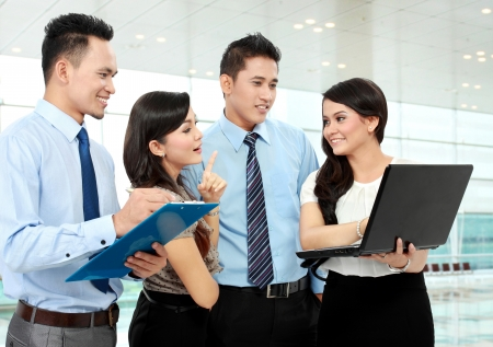 asian business people: group of happy business people doing presetation with laptop during meeting Stock Photo