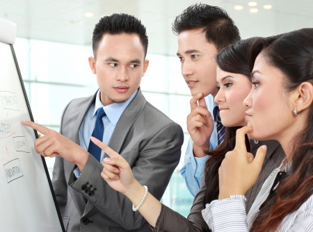 instrucciones: Grupo de hombres de negocios discutiendo y mirando a la pizarra en la oficina