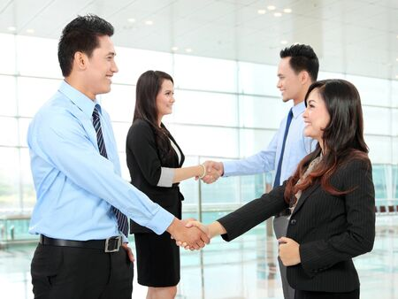 A business team with secretary in the office shaking hands photo
