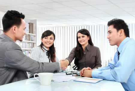 congratulating: Portrait of successful business team shaking hands with eachother in the office