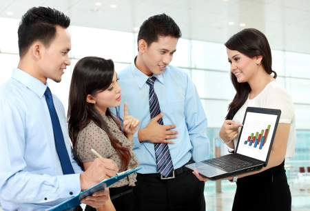 group of happy business people doing presetation with laptop during meeting photo