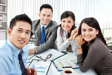 Portrait of business group meeting around a table with many paperwork Stock Photo - 17496242