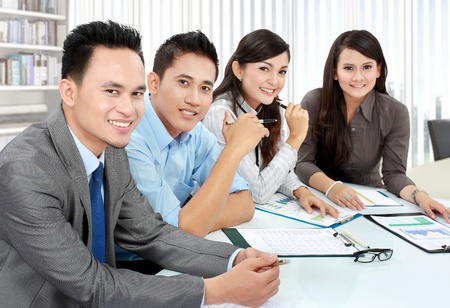 asian business team: Portrait of group executives meeting around a table with many paperwork