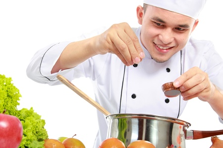 happy smiling male chef put some salt in the pan Stock Photo