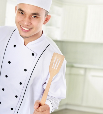 Portrait of confident male chef smiling in the kitchen photo