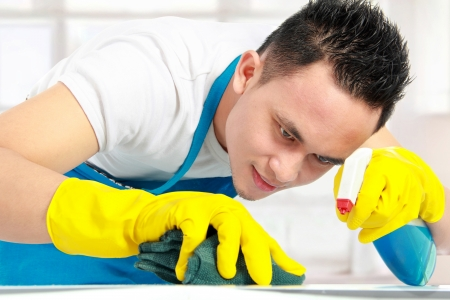 bright housekeeping: portrait of man doing some cleaning work in the house Stock Photo