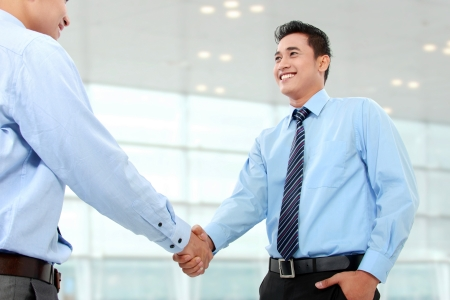 business deal: Portrait of successful business man shaking hands with eachother in the office