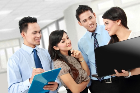 asian business team: group of happy business people doing presetation with laptop during meeting Stock Photo