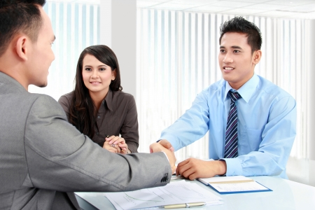 job satisfaction: Portrait of successful business team shaking hands with eachother in the office