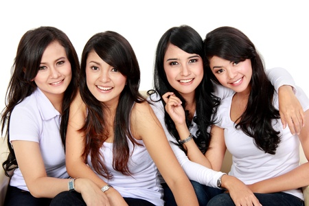 four friends: Group of beautiful women smiling isolated over a white background