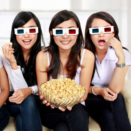 watching movie: girl friends sitting on couch watching movie in 3d